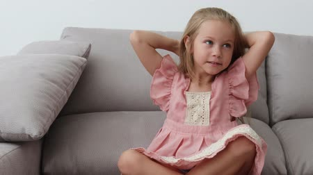 změť : cheerful girl of six years old in a pink dress sits on a sofa and brushes her blonde hair