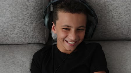 ouvir : boy in headphones laughs sitting looking at the camera, closeup