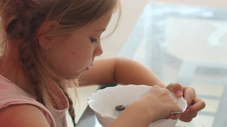 flocos de milho : Little blond girl eating Chocolate Cornflakes Cereal Bowl.Breakfast concept Stock Footage