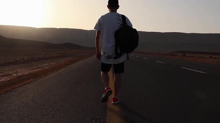 walking back : Wanderer or loner walks along an asphalt road, with a backpack on his back at sunset Stock Footage