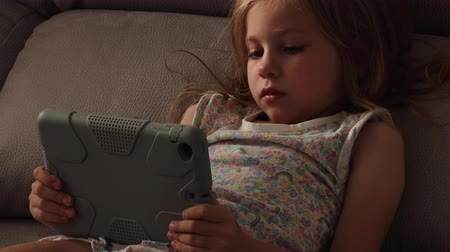 Beautiful little girl with gadget in bed at night. Bedtime schedule. closeup Stok Video