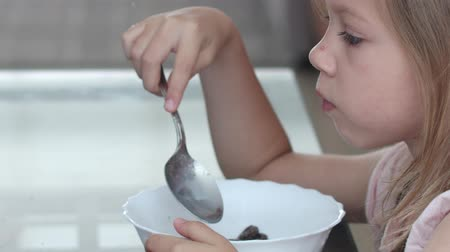 girl eats chocolate cereal with milk Stok Video