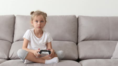 funny blonde girl without a tooth plays video games in a white t-shirt
