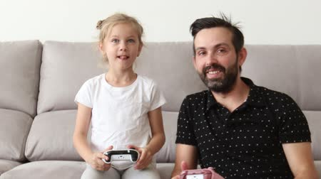 father and his cute little daughter are playing game console and smiling while sitting on couch