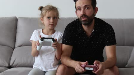 young father playing with his daughter in a video game and celebrating the victory. gives hi five Stok Video
