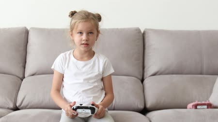 Girl Playing in Video Game Console, Using Joystick Controller. Happy blond girl Playing Video games