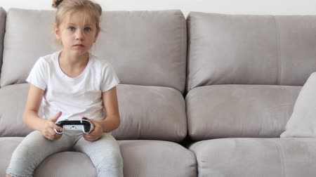 Competitive girl playing with gamepad on couch Stok Video