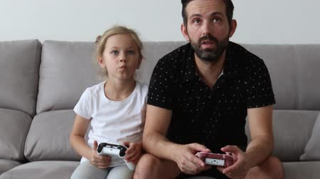 Father and young child are playing video game on couch at home, pressing buttons on joystick.