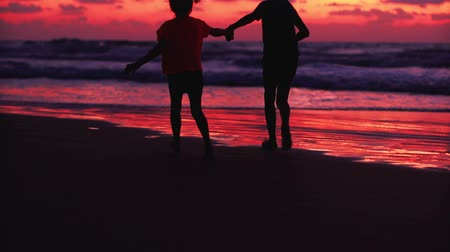 silhouettes of children run holding hands along the sea during sunset.