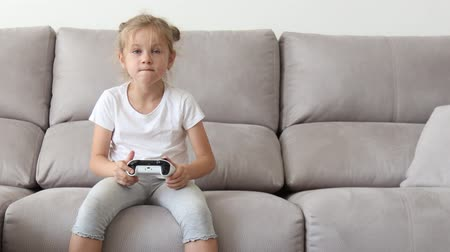контроллер : Enthusiastic kid in casual outfit playing with joystick while sitting on sofa in living-room. Стоковые видеозаписи