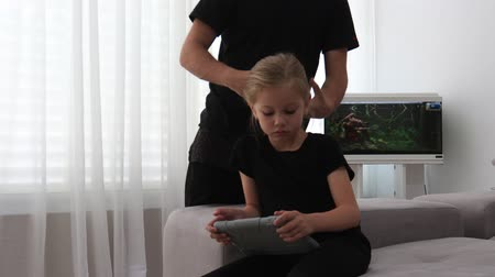 Dad combs his daughters hair while sitting on the couch. Dad and daughter spend time together