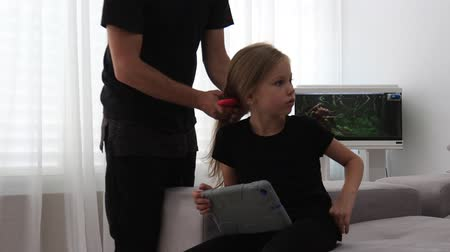 Cute little girl is smiling while her father is combing daughters hair