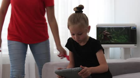 kartáč na vlasy : Mother combs cute daughter hair, which looks at tablet. Mother spends time with daughter