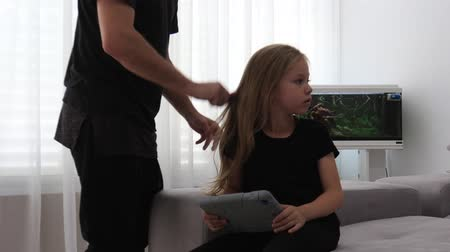 portrait of dad help her daughter to comb her hair at home Stok Video