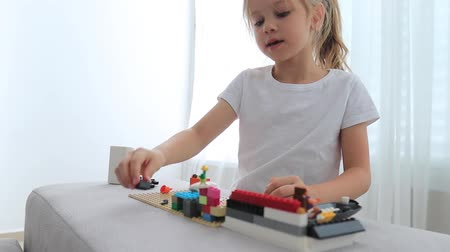 pré escolar : Charming preschooler playing with small constructor. Little girl playing with connecting toy cubes. Stock Footage