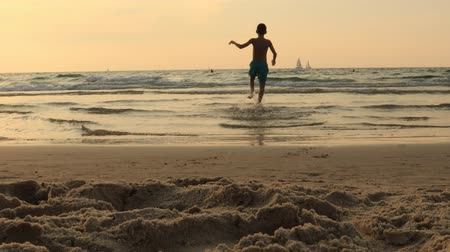 jump away : Boy child is jumping on a sea beach at sunset. Hyperactive boy run and jump on beach sand smiling.