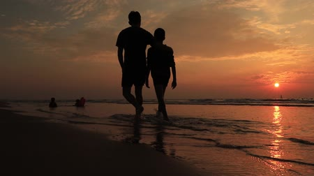 Father and son on the beach at sunset. Happy young family have fun on beach. run and jump at sunset Stockvideo