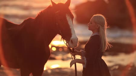 sivilceli : Blond woman wearing elegant long dress walking with horse on beautiful rocky seashore in sunlight