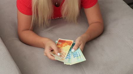 Womans two hands holding a fan of money of Israeli New Shekels, the new 200 and 100 shekel