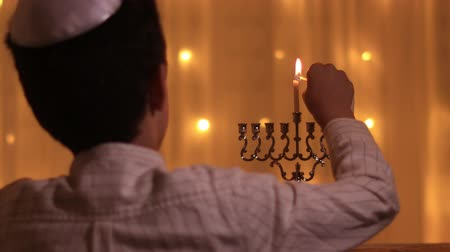 İbranice : rear view a Jewish boy lights a third menorah candle during the Jewish holiday of Hanukkah.