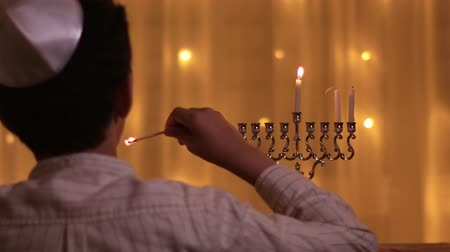 menorah : rear view of a young boy lights a second menorah candle during the Jewish holiday of Hanukkah