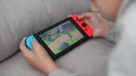 tel Aviv, Israel - January 01, 2020: close-up childrens hands holding a portable console Nintendo switch, a boy playing pokemon.