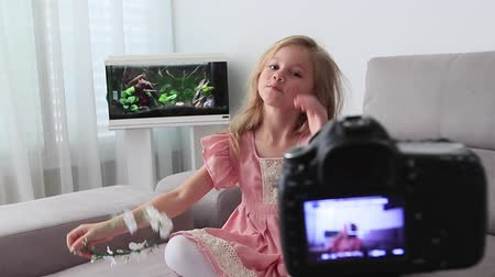Funny preschooler girl sit on couch look at camera waving having DSLR camera video blog conversation, smiling little child blogger shoot record video blog or vlog say hello to viewers subscribers