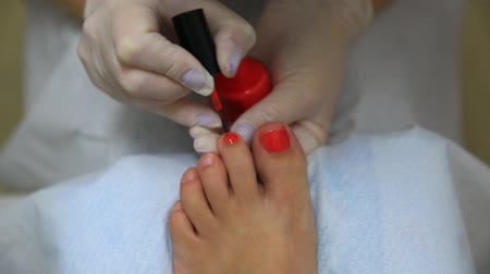 prosedür : master on a pedicure paints fingernails or nails on a leg or foot of the woman Stok Video