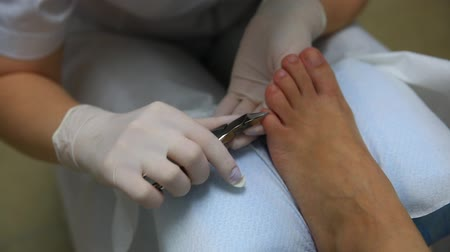 professional wellness : The master cares for the nails and feet of the client, doing the pedicure. Peeling feet pedicure procedure Stock Footage