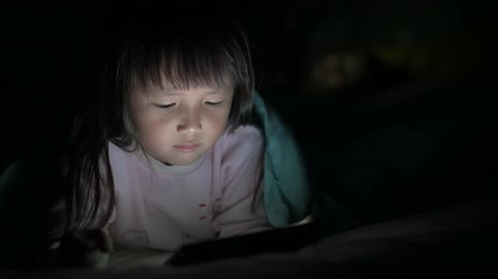 yansıyan : Little Girl are watching tablets in bed at night light flashes reflected from the screen, children using phones or playing tablet games, children using games with addiction and cartoon concepts