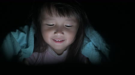 мультфильмы : Little Girl are watching tablets in bed at night light flashes reflected from the screen, children using phones or playing tablet games, children using games with addiction and cartoon concepts
