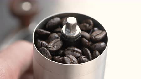 grattugia : Coffee beans in a hand grinder, closeup roasted coffee beans into a manual coffee grinder Filmati Stock