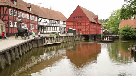 half timbered houses : Wide shoot of scene in the Old town where a small boat is ferrying people across the river and a horse carriage pass along the banks of the river