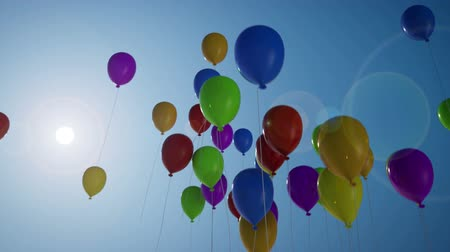 balonlar : 1080p HD stock video of multi-colored balloons, flying up into the deep blue sky. Stok Video