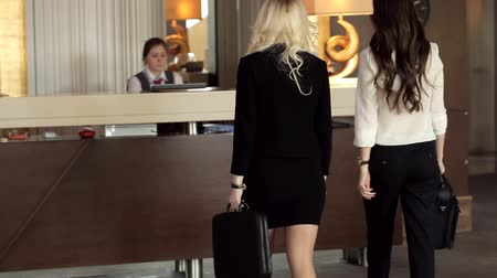 reception : Two young girls check in at hotel reception