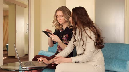 в чате : Two young girls sitting on sofa working with laptop and tablet Стоковые видеозаписи