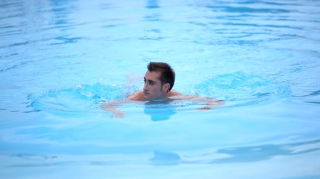 butterflies in the stomach : Muscular man swims in the pool