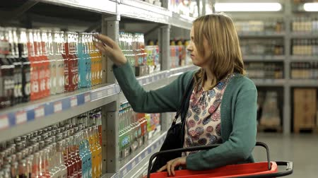choise : Woman chooses alcohol at the supermarket