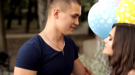 evet : Couple in love with balloons spends time together in a holiday park Stok Video