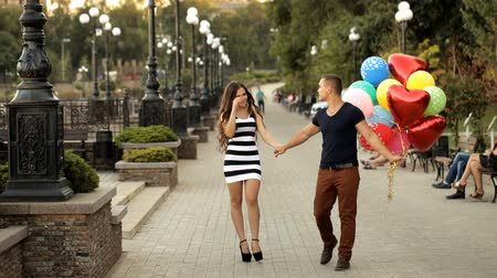 evet : Loving couple with balloons walking along the waterfront