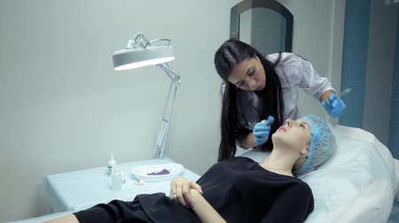 alargamento : In the clinic, a medical cosmetologist injects Botox with a girl to increase her lips