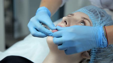 увеличение : The beautician smoothes botox in the lips of a young girl after the injection. Lip augmentation procedure.