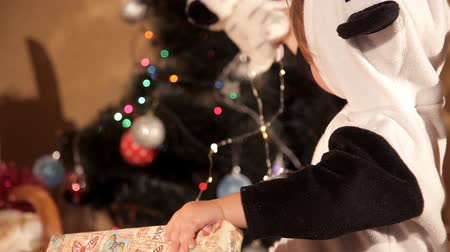 irmãs : Child opens a New Years gift near a Christmas tree