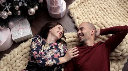 faház : Romantic evening on New Years Eve party. Spouses spend time together, lying near the Christmas tree Stock mozgókép