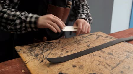 přezka : With an industrial knife, the master cuts off excess skin on the workpiece under the belt. Procedure for the manufacture of leather belts Dostupné videozáznamy