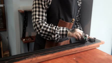 řemeslníci : In the workshop, a specialist colors the belt in black. Procedure for the manufacture of leather belts