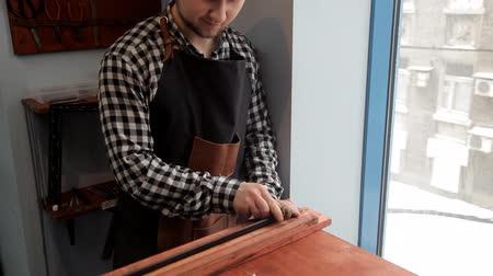 aşınmış : In the workshop, a specialist sharpens a leather belt. Procedure for the manufacture of leather belts