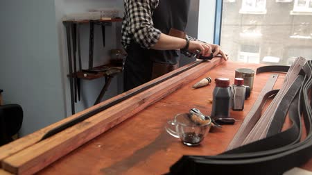 hound : The master processes the edges on the leather strap with a special tool