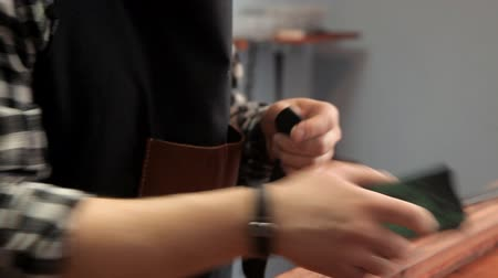 desenli : The master processes the edges on the leather strap with a special tool
