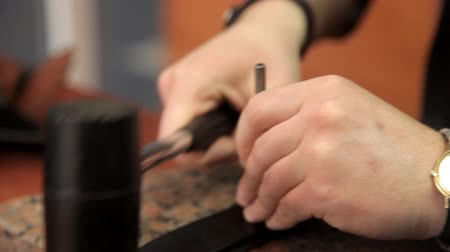 spona : The master makes holes in the leather belt. Leather belt manufacturing